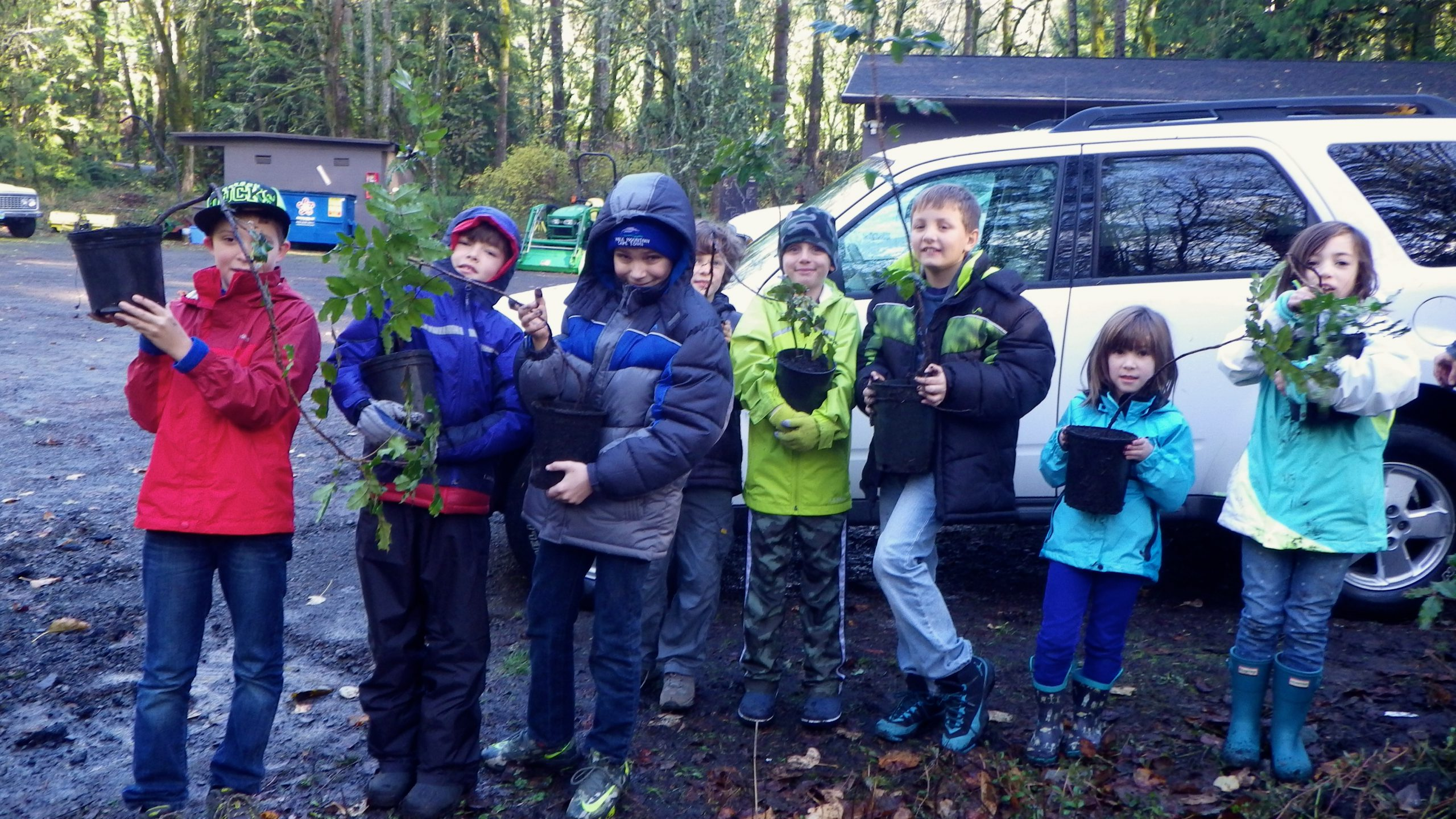 Group of 8 children outdoors wearing jackets holding potted native plants.