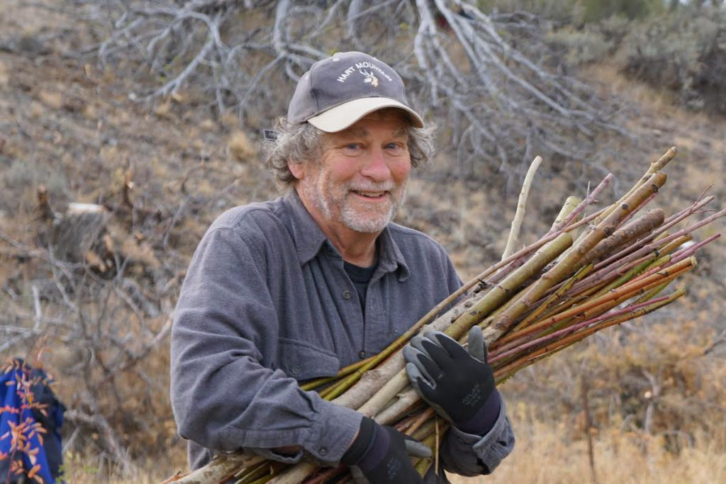 Board member Carl Axelsen, smiling and carrying a bundle of sticks.