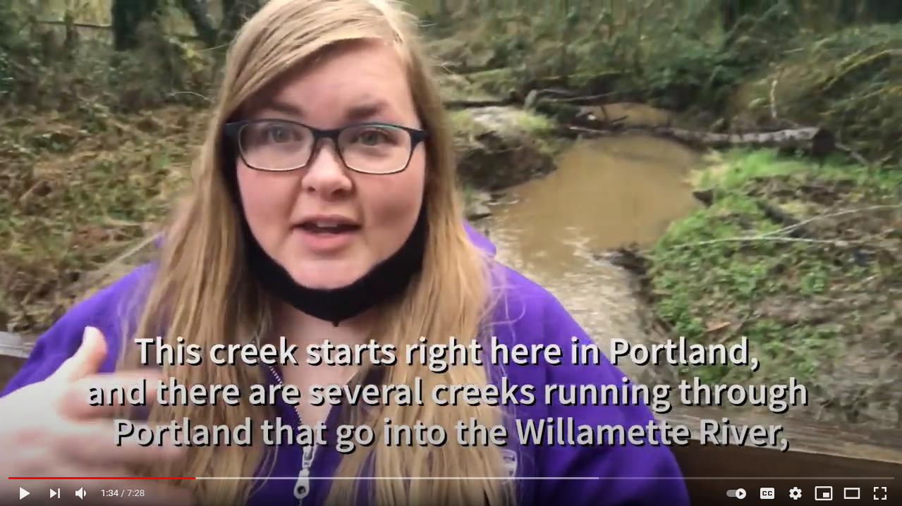 A screenshot of a video, where TCWC'S Coordinator stands on a bridge with Tryon Creek in the background.
